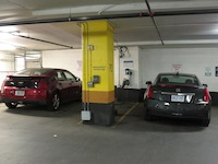2014 Cadillac ELR Graphite Gray and red chevrolet volt plugged in at a charging station