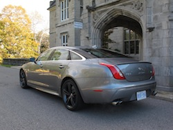 2014 Jaguar XJR L Silver rear side view in front of castle
