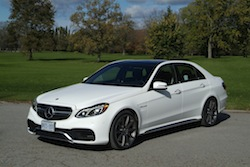 2014 Mercedes E63 AMG S White front view grass headlights