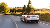 bmw 228i cabriolet driving in the sunset